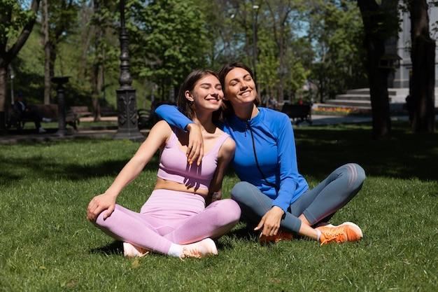 Dos mujeres bonitas en ropa deportiva sobre el césped en el parque en un día soleado haciendo yoga se abrazan con una sonrisa en la cara