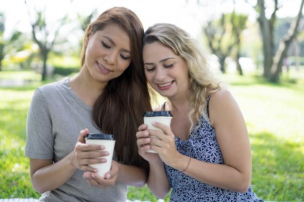Dos mujeres bonitas sonrientes que sostienen las tazas de café plásticas en parque