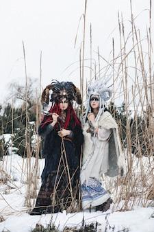 Dos mujeres brujas en ropa de fantasía y coronas de pie en la nieve del invierno