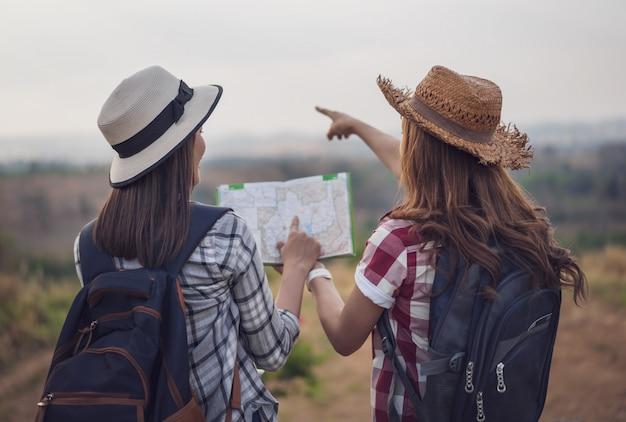 Dos mujeres buscando la dirección en el mapa de ubicación mientras viaja