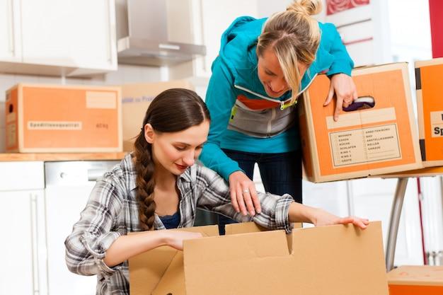 Dos mujeres con caja móvil en su casa