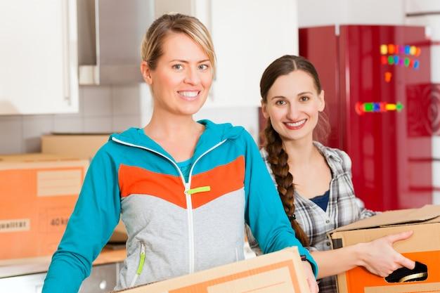 Dos mujeres con caja de mudanza en su casa