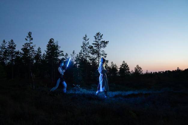 Dos mujeres caminan por la noche en un pantano usando una lámpara led para seguir el rastro de una sesión de fotos de moda futurista