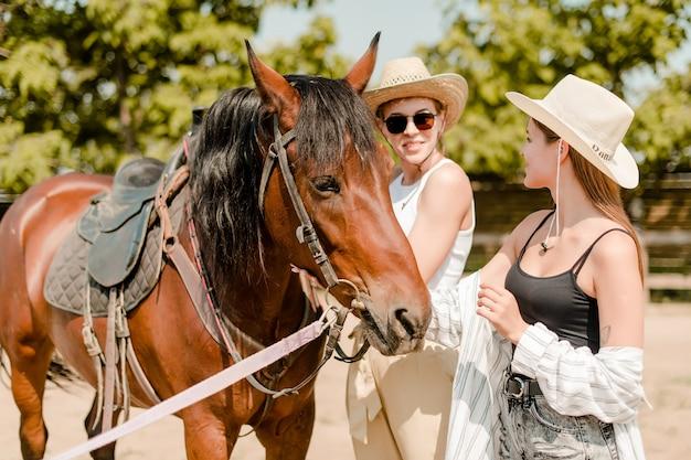 Dos mujeres de campo en la granja con un caballo