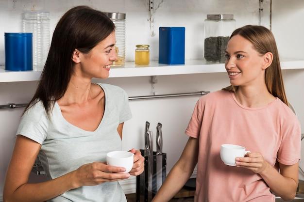 Dos mujeres en casa en la cocina charlando con un café