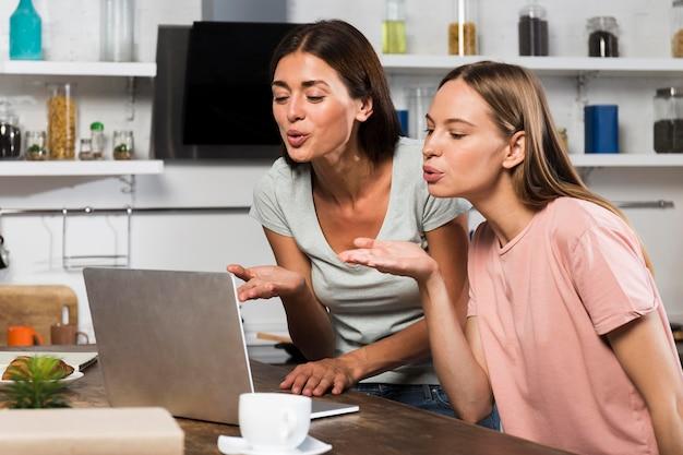 Dos mujeres en casa video chat en portátil