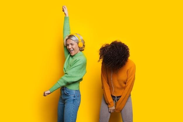 Dos mujeres caucásicas de pelo rizado bailan mientras escuchan música