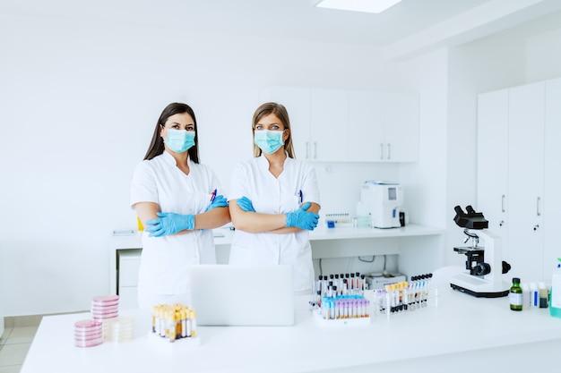 Dos mujeres caucásicas seguras asistentes de laboratorio en uniformes blancos