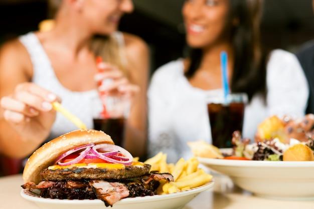 Dos mujeres comiendo hamburguesas y bebiendo refrescos