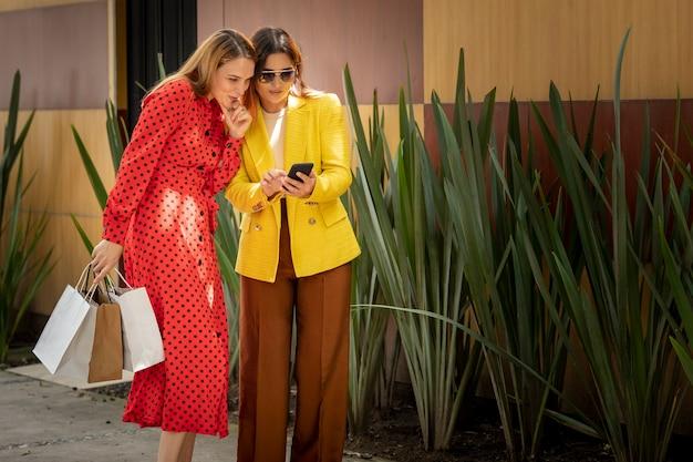 Dos mujeres de compras comprobando su teléfono celular en busca de una dirección en la aplicación
