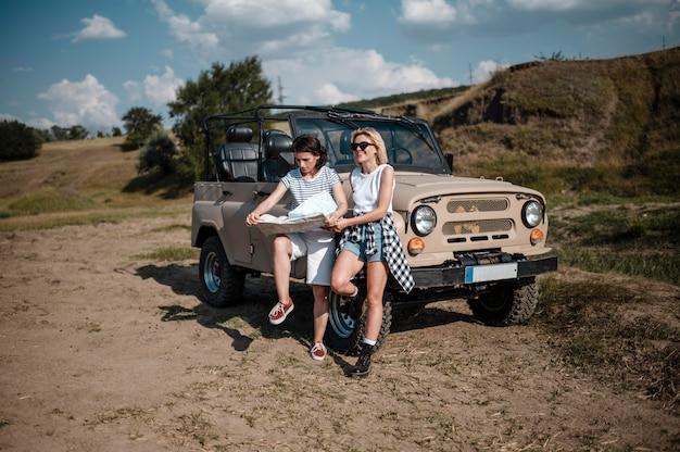Dos mujeres comprobando el mapa mientras viaja en coche