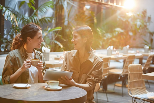Dos mujeres contemporáneas en la mesa de café