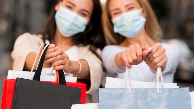 Dos mujeres desenfocadas con máscaras médicas posando junto con bolsas de la compra.