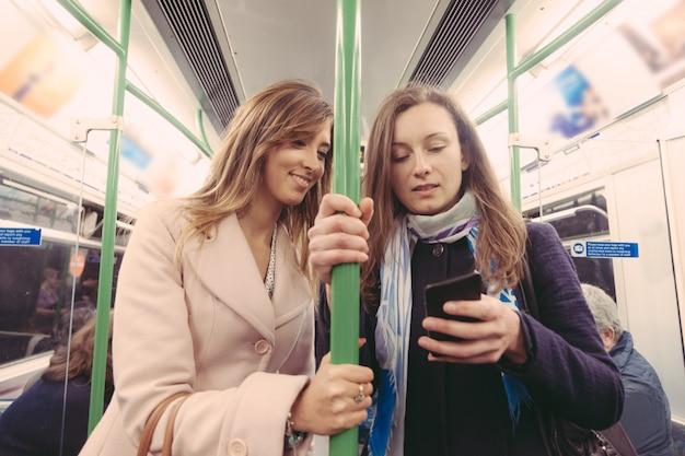 Dos mujeres desplazándose en metro en londres.