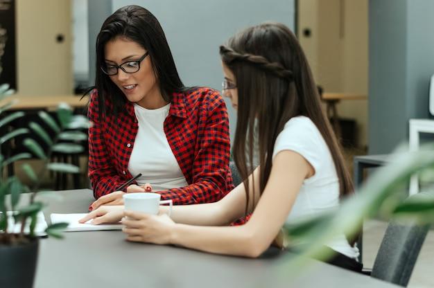 Dos mujeres discutiendo sobre documentos en la oficina.