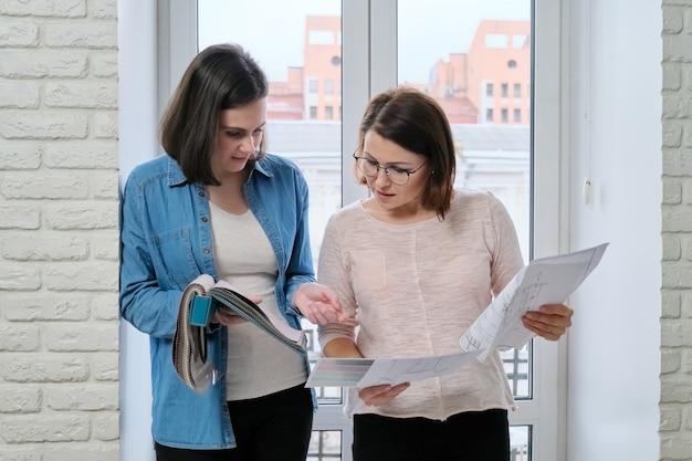 Dos mujeres diseñador y cliente que trabajan eligiendo telas para cortinas, tapicería de muebles