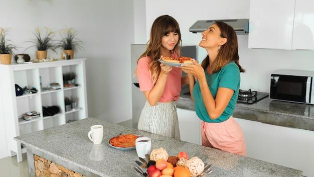 Dos mujeres disfrutando de pizza en la cocina en el moderno apartamento.