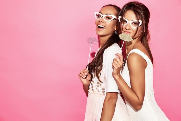 Dos mujeres divertidas sorprendidas en vasos de papel y labios grandes en palo. concepto inteligente y de belleza. alegres modelos jóvenes listos para la fiesta. mujeres aisladas en la pared rosa. hembra positiva