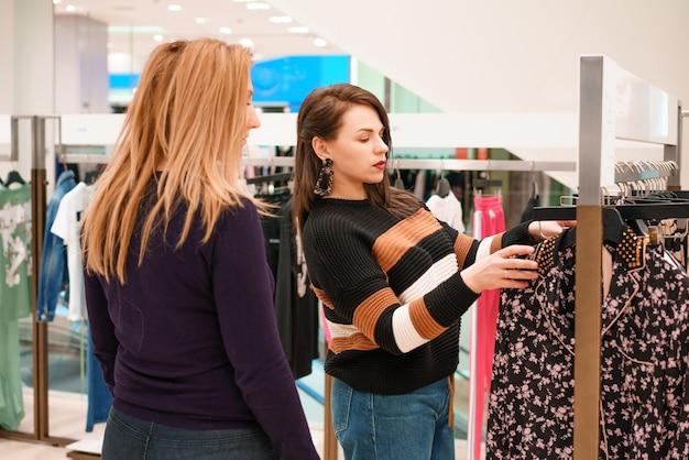 Dos mujeres eligen ropa en una tienda.