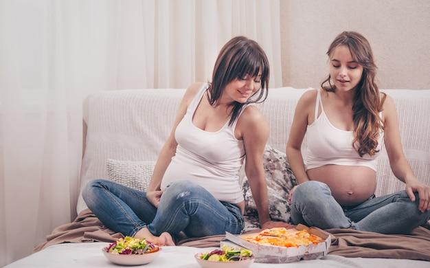Dos mujeres embarazadas comiendo pizza y ensalada en casa