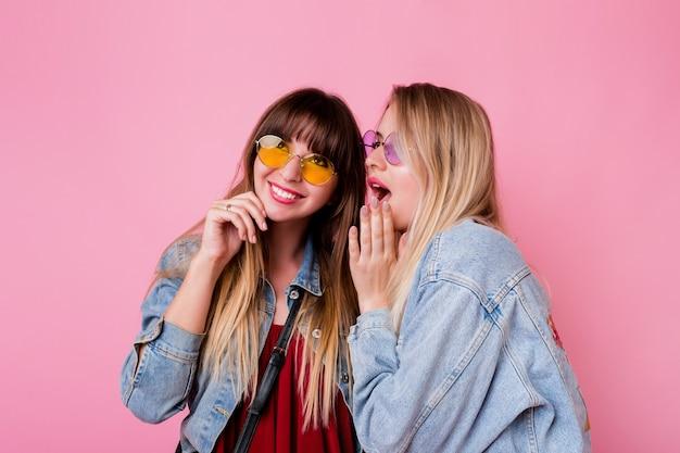 Dos mujeres emocionadas chismean en la pared rosa