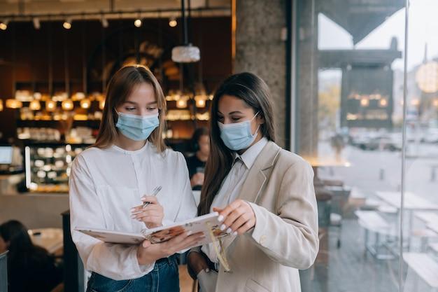 Dos mujeres empresarias con sus máscaras faciales debatiendo diferentes puntos de vista sobre el trabajo