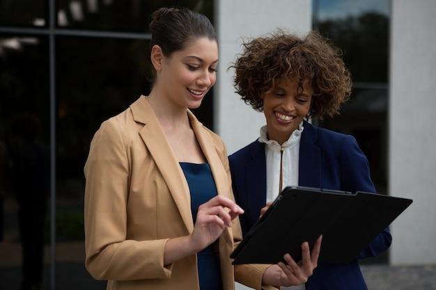 Dos mujeres empresarias con tableta digital cerca del edificio de oficinas