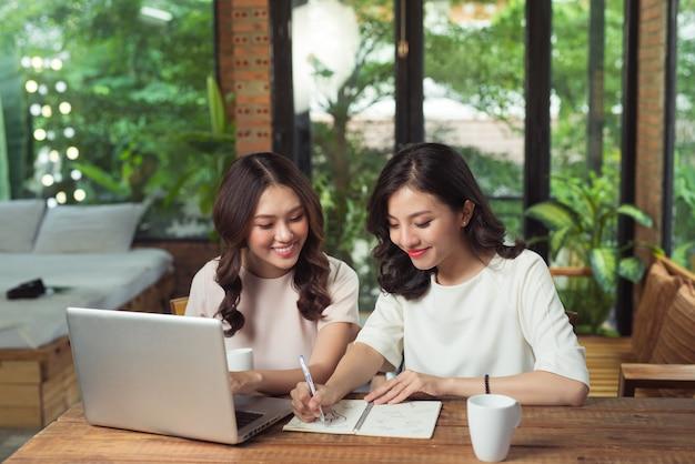 Dos mujeres empresarias trabajando juntas. chica está sentada a la mesa delante de la computadora portátil