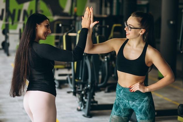Dos mujeres entrenando juntas en el gimnasio