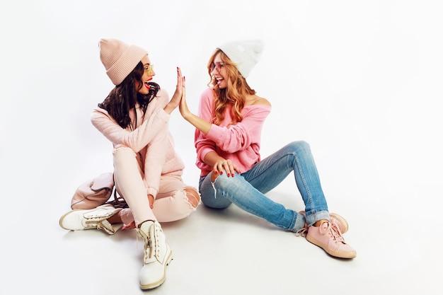 Dos mujeres entusiastas en un hermoso traje de invierno rosa, sombreros rosados y suéteres relajándose en el piso, divirtiéndose sobre fondo blanco.