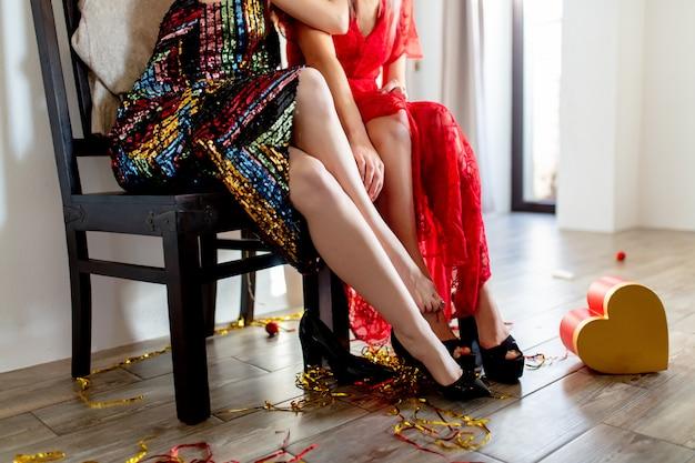 Dos mujeres están coqueteando a pies en una fiesta de san valentín