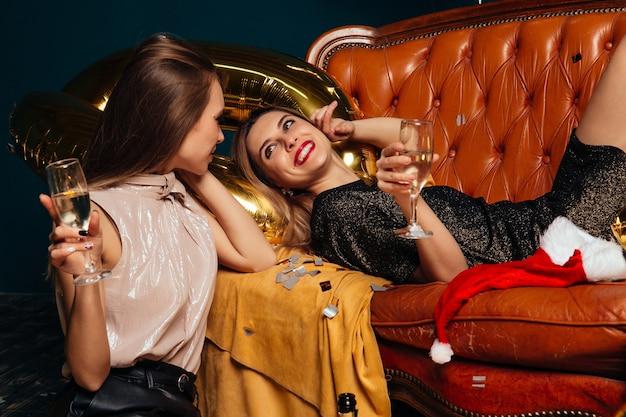 Dos de las mujeres con estilo felices celebrando con champán y se divierten en la celebración