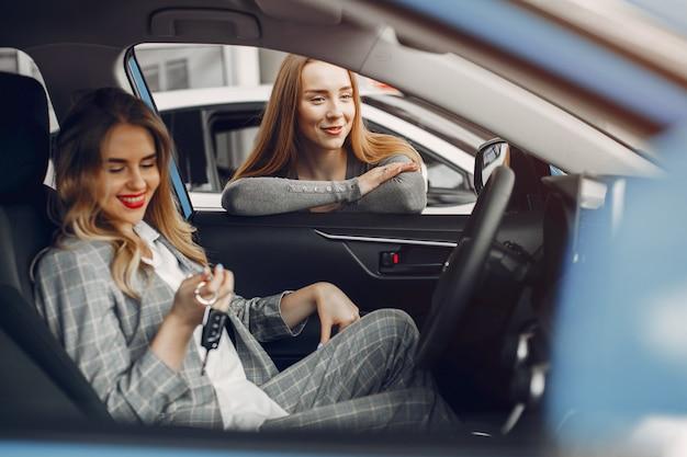Dos mujeres con estilo en un salón de autos