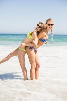 Dos mujeres felices en bikini y gafas de sol divirtiéndose en la playa