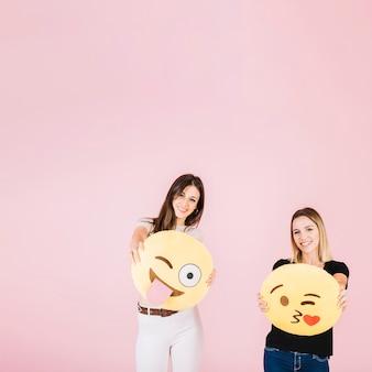 Dos mujeres felices con diferentes iconos de emoji sobre fondo rosa