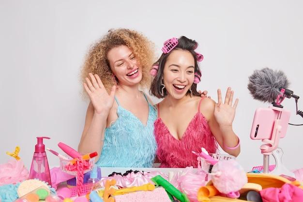 Dos mujeres felices y diversas filman un tutorial de maquillaje diario con las palmas de las olas saludan a los seguidores, disfrutan de la transmisión en vivo, se preparan para una ocasión especial, hacen el peinado con rodillos transmitiendo en un teléfono inteligente