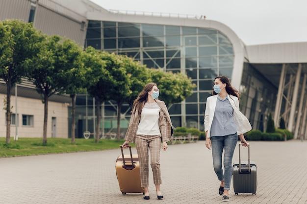 Dos mujeres felices con máscaras protectoras después de la cuarentena por coronavirus con maletas van al aeropuerto