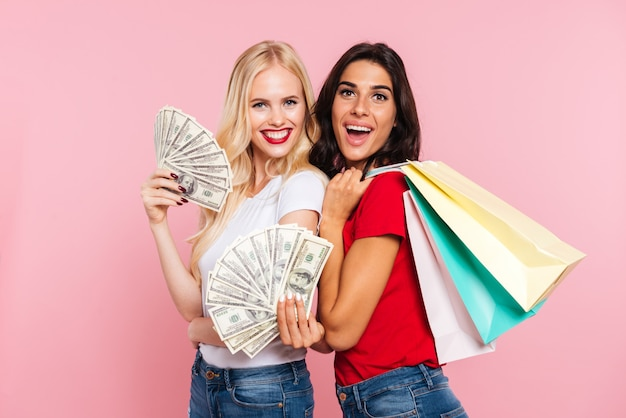 Dos mujeres felices posando con dinero y paquetes mientras mira a la cámara en rosa
