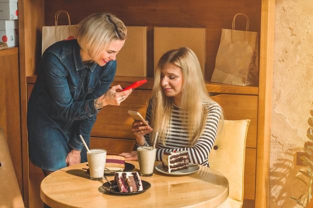 Dos mujeres felices sentadas en un café y tomando selfies en el teléfono, bebiendo un cóctel, contando historias divertidas, estando de buen humor, riendo felices. mejores amigos