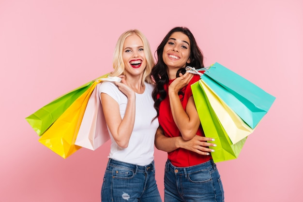 Dos mujeres felices sosteniendo paquetes en los hombros y mirando a la cámara sobre rosa