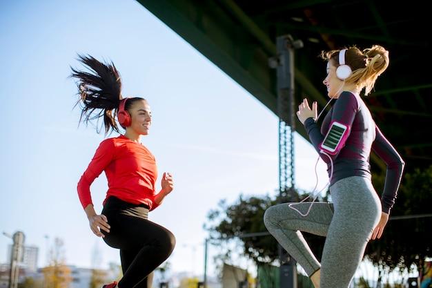 Dos mujeres fitness haciendo ejercicio antes de correr al aire libre