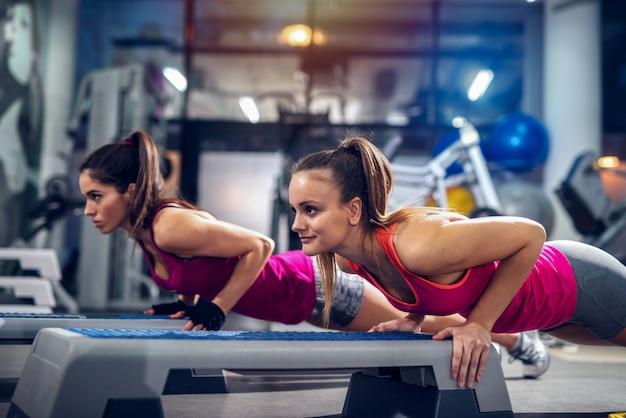Dos mujeres en un gimnasio haciendo flexiones en un stepper. fuerte y dedicado.