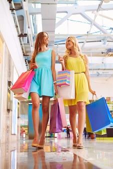 Dos mujeres guapas caminando por el centro comercial después de las compras