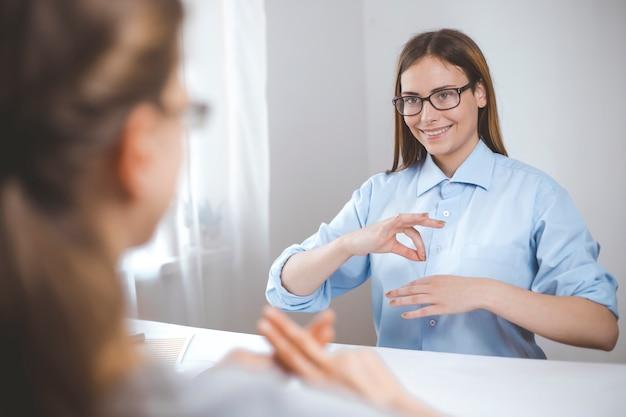 Dos mujeres hablan lenguaje de señas. niñas para hablar el lenguaje de personas con discapacidad auditiva, sordas.