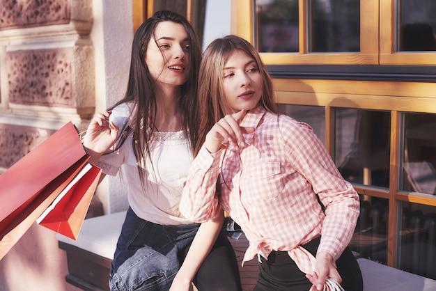 Dos mujeres hablando después de hacer compras en la calle cerca de la ventana.