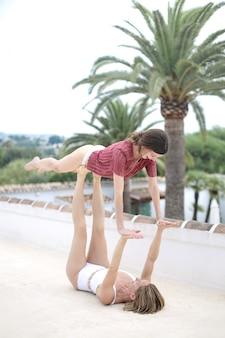 Dos mujeres haciendo yoga aéreo