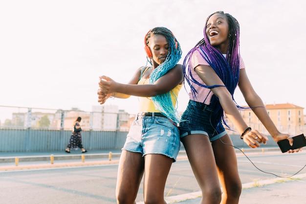 Dos mujeres hermanas al aire libre escuchando música bailando