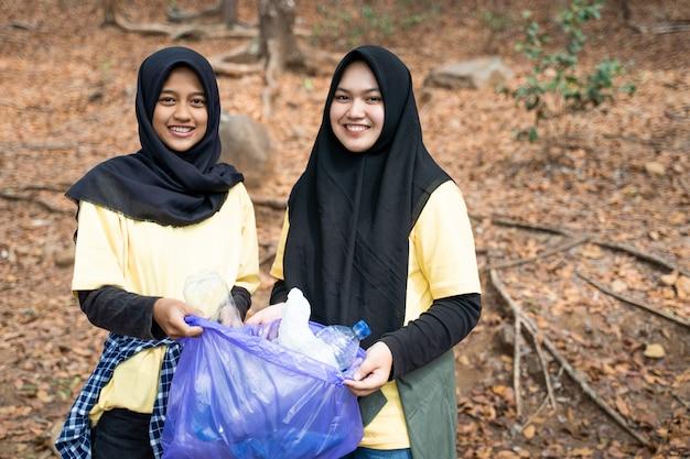 Dos mujeres hijab sonriente voluntario con bolsa de basura