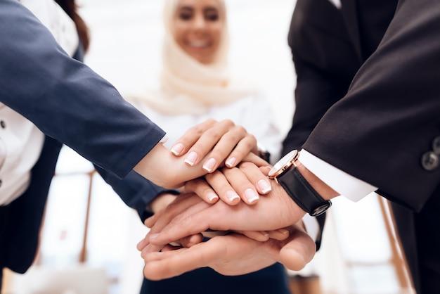 Dos mujeres y un hombre se dan la mano.
