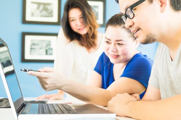 Dos mujeres y un hombre están mirando felizmente la computadora en la oficina moderna